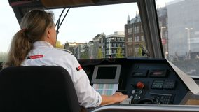Amsterdam, Netherlands - April 22, 2019: Woman captain controls the tourist boat. Amsterdam waterway walk in evening stock video footage