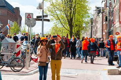 AMSTERDAM,NETHERLANDS-APRIL 27: Young couple in orange take picture around red light district on King's Day in Amsterdam. Royalty Free Stock Photos