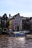 AMSTERDAM, NETHERLANDS - AUGUST 6, 2016: Famous buildings of Amsterdam city centre close-up. General landscape view of city street. S and traditional Dutch Royalty Free Stock Image