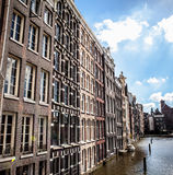 AMSTERDAM, NETHERLANDS - AUGUST 6, 2016: Famous buildings of Amsterdam city centre close-up. General landscape view of city street Royalty Free Stock Photography