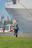 Amsterdam, Netherlands - August 20: SAIL 2015, woman takes a picture of a naval ship Royalty Free Stock Photos