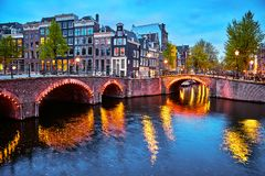 Amsterdam, Netherlands. Bridges with nighttime illumination. Over canals with water in Old town. Quarter with traditional dutch houses. Evening landscape. Blue royalty free stock photo