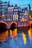 Amsterdam, Netherlands. Bridges with nighttime illumination. Over canals with water in Old town. Quarter with traditional dutch houses. Vertical evening royalty free stock photo