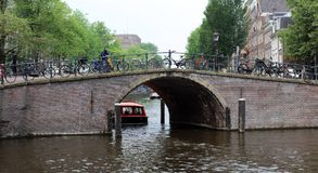 Amsterdam, The Netherlands, city canals, boats, bridges and streets. Unique beautiful and wild European city. Red light district, erotic city. Bicycles vintage Stock Photography