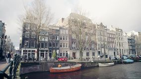 AMSTERDAM, NETHERLANDS - DECEMBER 25, 2017. Bridge over city canal. AMSTERDAM, NETHERLANDS - DECEMBER 25, 2017 Typical canal and houses stock footage