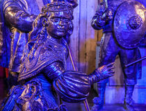 AMSTERDAM, NETHERLANDS - DECEMBER 19, 2015: Bronze figures of soldiers on central square of city lit with street light at night on Royalty Free Stock Photography
