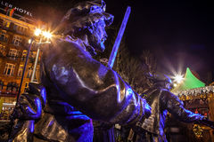 AMSTERDAM, NETHERLANDS - DECEMBER 19, 2015: Bronze figures of soldiers on central square of city lit with street light at night on Stock Images