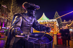 AMSTERDAM, NETHERLANDS - DECEMBER 19, 2015: Bronze figures of soldiers on central square of city lit with street light at night on Stock Photo