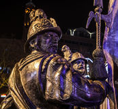 AMSTERDAM, NETHERLANDS - DECEMBER 19, 2015: Bronze figures of soldiers on central square of city lit with street light at night on Royalty Free Stock Images