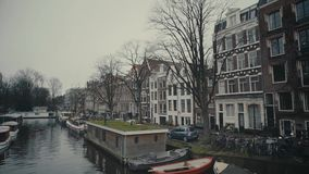 AMSTERDAM, NETHERLANDS - DECEMBER 26, 2017. City canal and moored boat houses. AMSTERDAM, NETHERLANDS - DECEMBER 26, 2017 Canal and boat houses stock footage