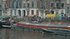AMSTERDAM, NETHERLANDS - DECEMBER 26, 2017. City canal embankments and moored boats. AMSTERDAM, NETHERLANDS - DECEMBER 26 2017 Canal and boats stock video footage