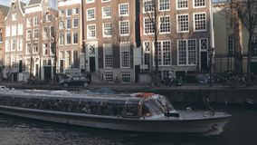 AMSTERDAM, NETHERLANDS - DECEMBER 27, 2017. Canal tour boat and traditional houses. AMSTERDAM, NETHERLANDS - DECEMBER 27 2017 Canal tour boat stock video footage