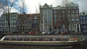 AMSTERDAM, NETHERLANDS - DECEMBER 26, 2017. Boat sightseeing tour on city canal. AMSTERDAM, NETHERLANDS - DECEMBER 26 2017 City canal stock video footage