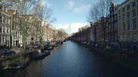 AMSTERDAM, NETHERLANDS - DECEMBER 26, 2017. City canal and embankments on a sunny winter day. AMSTERDAM, NETHERLANDS - DECEMBER 26, 2017 City canal and stock video