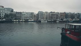 AMSTERDAM, NETHERLANDS - DECEMBER 26, 2017. City canal pan shot. AMSTERDAM, NETHERLANDS - DECEMBER 26 2017 City canal stock video footage