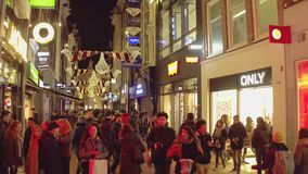 AMSTERDAM, NETHERLANDS - DECEMBER 28, 2017. Crowded street and lit storefronts in the evening. AMSTERDAM, NETHERLANDS - DECEMBER 28, 2017 Crowded street and stock footage