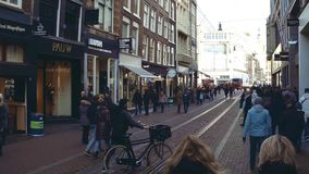 AMSTERDAM, NETHERLANDS - DECEMBER 27, 2017. Crowded tourist street. AMSTERDAM, NETHERLANDS - DECEMBER 27 2017 Tourist street stock video footage