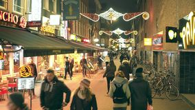 AMSTERDAM, THE NETHERLANDS - DECEMBER 25, 2017. Walk along crowded tourist street decorated for Christmas and New Year. AMSTERDAM, THE NETHERLANDS - DECEMBER 25 stock footage