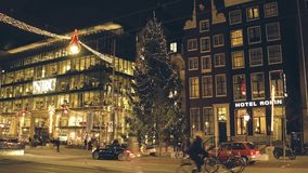 AMSTERDAM, NETHERLANDS - DECEMBER 28, 2017. Big decorated Christmas tree and night traffic on Rokin major street. AMSTERDAM, NETHERLANDS - DECEMBER 28, 2017 stock video footage