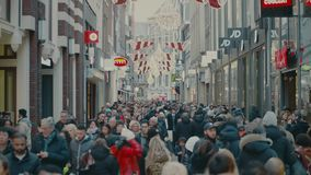 AMSTERDAM, THE NETHERLANDS - DECEMBER 25, 2017. Overhead steadicam shot of crowded tourist street in city center. AMSTERDAM, THE NETHERLANDS - DECEMBER 25, 2017 stock footage