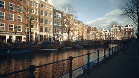 AMSTERDAM, NETHERLANDS - DECEMBER 26, 2017. People cycling along city canal embankment. AMSTERDAM, NETHERLANDS - DECEMBER 26, 2017 People cycling along city stock video