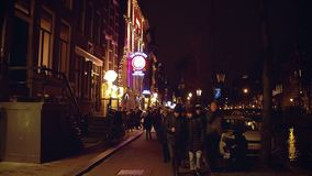 AMSTERDAM, NETHERLANDS - DECEMBER 27, 2017. POV walk along crowded city canal embankment in the evening. AMSTERDAM, NETHERLANDS - DECEMBER 27 2017 City canal stock video