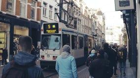 AMSTERDAM, NETHERLANDS - DECEMBER 27, 2017. Crowded tourist street and moving tram. AMSTERDAM, NETHERLANDS - DECEMBER 27, 2017 Tourist street and moving tram stock footage