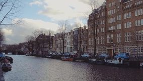 AMSTERDAM, THE NETHERLANDS - DECEMBER 25, 2017. City canal embankment and the Dutch houses facades. AMSTERDAM, THE NETHERLANDS - DECEMBER 25, 2017 Typical canal stock video