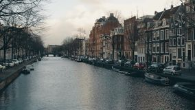 AMSTERDAM, NETHERLANDS - DECEMBER 26, 2017. View from the bridge over city canal. AMSTERDAM, NETHERLANDS - DECEMBER 26, 2017. View from the bridge over canal stock footage