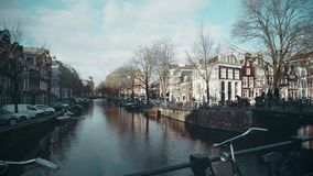 AMSTERDAM, NETHERLANDS - DECEMBER 26, 2017. Walk along the bridge over city canal. AMSTERDAM, NETHERLANDS - DECEMBER 26 2017 City canal stock video footage