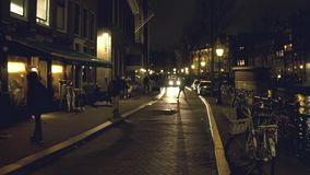 AMSTERDAM, NETHERLANDS - DECEMBER 26, 2017. Walk along the city canal embankment in the evening. AMSTERDAM, NETHERLANDS - DECEMBER 26, 2017 Walk along the canal stock video