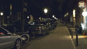 AMSTERDAM, NETHERLANDS - DECEMBER 26, 2017. POV walk along the canal embankment in the evening. AMSTERDAM, NETHERLANDS - DECEMBER 26, 2017 Walk along the canal stock video footage