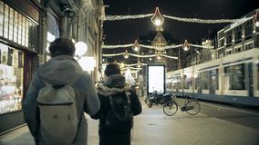 AMSTERDAM, THE NETHERLANDS - DECEMBER 25, 2017. Tourists with backpacks walk along city major street decorated for. AMSTERDAM, THE NETHERLANDS - DECEMBER 25 stock video footage