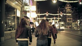 AMSTERDAM, NETHERLANDS - DECEMBER 25, 2017. Young people walk along city major street decorated for Christmas and New. AMSTERDAM, NETHERLANDS - DECEMBER 25, 2017 stock footage
