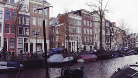 AMSTERDAM, THE NETHERLANDS - DECEMBER 25, 2017. Walk along typical city canal embankment and the Dutch houses facades. AMSTERDAM, THE NETHERLANDS - DECEMBER 25 stock video