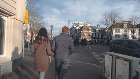 AMSTERDAM, NETHERLANDS - DECEMBER 26, 2017. Young couple walking along typical street in the city. AMSTERDAM, NETHERLANDS - DECEMBER 26, 2017 Couple walking stock video