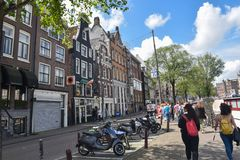 Amsterdam, Netherlands, Europe - July 27, 2017. Picturesque houses on a busy street in the city center of Amsterdam. Amsterdam, Netherlands, Europe - July 27 Royalty Free Stock Image