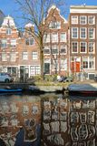 AMSTERDAM, NETHERLANDS - FEBRUARY 23, 2019: Reflection of crooked and colorful heritage buildings along Egelantiersgracht Canal stock images