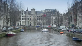 AMSTERDAM, THE NETHERLANDS - JANUARY 22, 2015: Canal and historic houses at Herengracht. A cityscape shot of a canal and historic houses at Herengracht. The flag stock footage