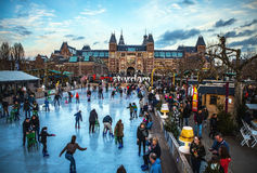 AMSTERDAM, THE NETHERLANDS - JANUARY 15, 2016: Many people skate on winter ice skating rink in front of the Rijksmuseum, a popular Royalty Free Stock Photos