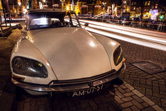 AMSTERDAM, NETHERLANDS - JANUARY 5, 2016: Vintage white car parked in center of Amsterdam at night time. January 5, 2016 in Amster. Dam - Netherland Royalty Free Stock Images