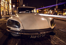 AMSTERDAM, NETHERLANDS - JANUARY 5, 2016: Vintage white car parked in center of Amsterdam at night time. January 5, 2016 in Amster. Dam - Netherland Stock Photo