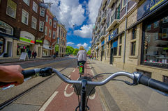 Amsterdam, Netherlands - July 10, 2015: Bikers point of view as bicycling through city streets on a beautiful sumer day Royalty Free Stock Image