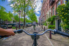 Amsterdam, Netherlands - July 10, 2015: Bikers point of view as bicycling through city streets on a beautiful sumer day Royalty Free Stock Photos