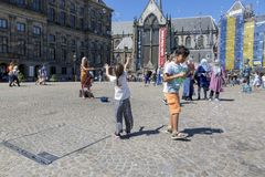 Children catch soap bubbles in the central Dam Square in Amsterdam. Amsterdam, Netherlands - July 02, 2018: Children catch soap bubbles in the central Dam Square stock photography