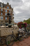 AMSTERDAM- NETHERLANDS, on JULY 12, 2017.Cycles and flowers near Statue of Lady Fortune, Amsterdam, Netherlands, Europe. Royalty Free Stock Images