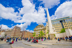 Amsterdam, Netherlands - July 10, 2015: Dam Square on a beautiful sunny day, tall monument and historical buildings Royalty Free Stock Image