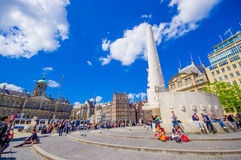 Amsterdam, Netherlands - July 10, 2015: Dam Square on a beautiful sunny day, tall monument and historical buildings Royalty Free Stock Photos