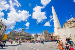 Amsterdam, Netherlands - July 10, 2015: Dam Square on a beautiful sunny day, tall monument and historical buildings Royalty Free Stock Photography