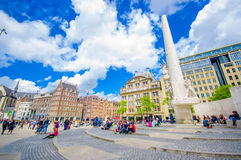 Amsterdam, Netherlands - July 10, 2015: Dam Square on a beautiful sunny day, tall monument and historical buildings Royalty Free Stock Images